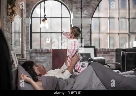 Couple lying in bed playing with her little daughter - Stock Photo