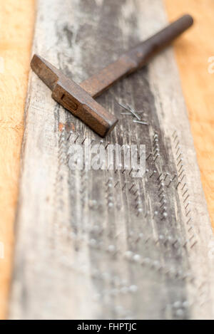 Handcraft art decoration board  with letters  made of nails with hammer - Stock Photo