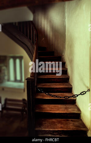 Old staircase wit a chain blocking the way up - Stock Photo