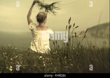 young woman sitting on cliff waving and holding grass awaiting her lover - Stock Photo