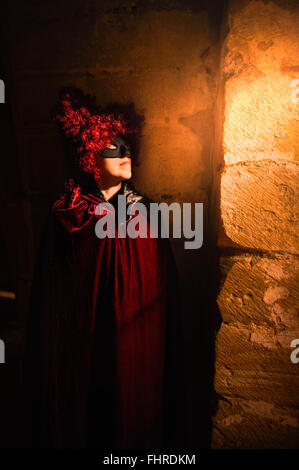 female figure wearing red wig  standing in castle by the window - Stock Photo