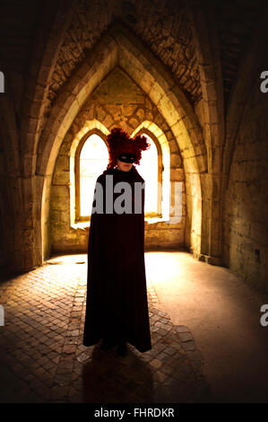 female figure wearing red wig  standing in castle - Stock Photo