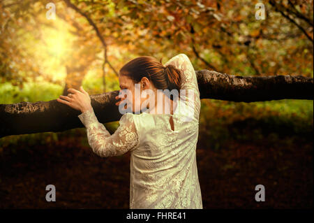 young woman in park leaning on tree branch - Stock Photo