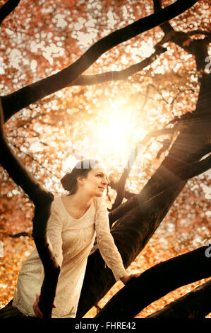 young beautiful woman sitting on tree branch - Stock Photo