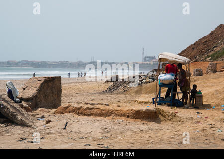 ACCRA, GHANA - JANUARY 2016: Food stall surrounded by people on the beach in Accra, Ghana at the Gulf of Guinea - Stock Photo