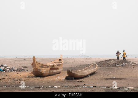 ACCRA, GHANA - JANUARY 2016: People and fishing boats on a beach in Jamestown, Accra, Ghana at the Gulf of Guinea - Stock Photo