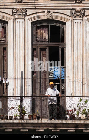 Daily life in Cuba - Cuban senior man leaning on balcony railings at Havana, Cuba, West Indies, Caribbean, Central - Stock Photo
