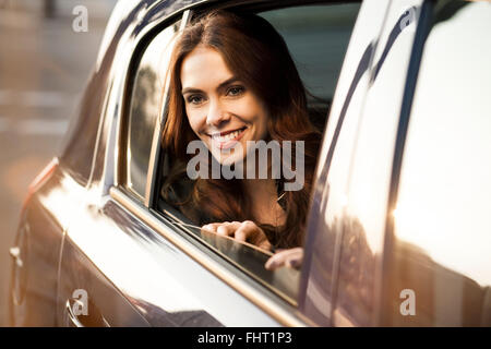 Smiling young woman looking out of car window - Stock Photo