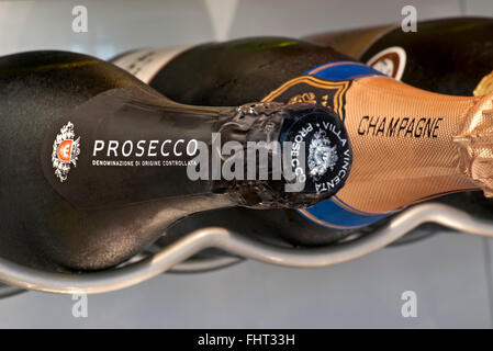 Prosecco and Champagne sparkling wine bottles stored horizontally in chilled temperature controlled wine cabinet - Stock Photo