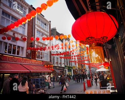 Chinese lanterns lit up by sunset on a busy shopping day in Chinatown Soho London UK - Stock Photo