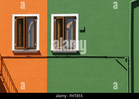 A house on the island of Burano close Venice with two identical windows and orange green painting in daylight. Stock Photo