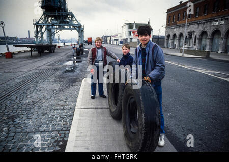 Young boys playing with discarded truck tyres outside the Point Depot on the Quays in Dublin city, mid 1980's. Scan - Stock Photo