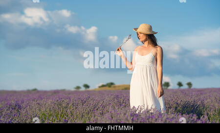 Beautiful young woman wearing a white dress standing in the middle of a lavender field holding a few blades of  - Stock Photo