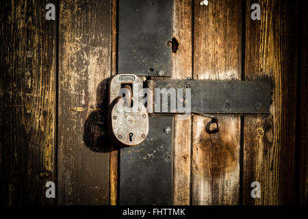 'padlock on an old wooden door of a shed - Stock Photo