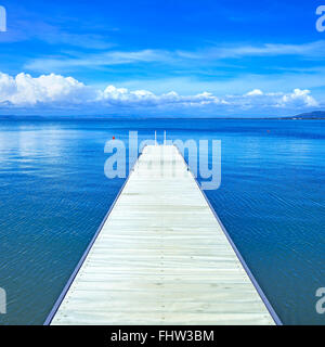 Wooden pier or jetty on a blue ocean and clear sky. Bay beach in Monte Argentario, Porto Santo Stefano, Tuscany, - Stock Photo