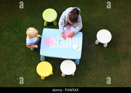 Fun outdoor activities. Creative fun way to boredom. Children play in the garden, they draw with crayons - Stock Photo