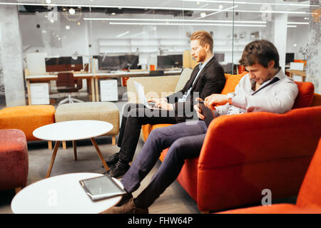 Businesspeople working while looking at devices and  laptops - Stock Photo