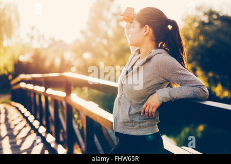 Beautiful female tired after jogging taking a break - Stock Photo