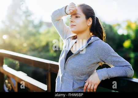 Beautiful woman resting after jogging outdoors and being exhausted - Stock Photo