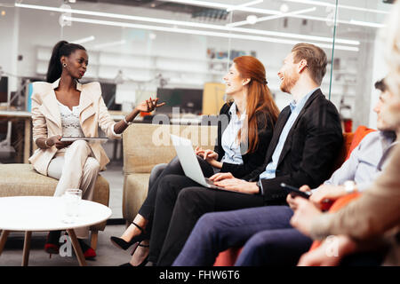 Business people conversation with technology at hand. Exchange of new ideas and brainstorming between colleagues - Stock Photo