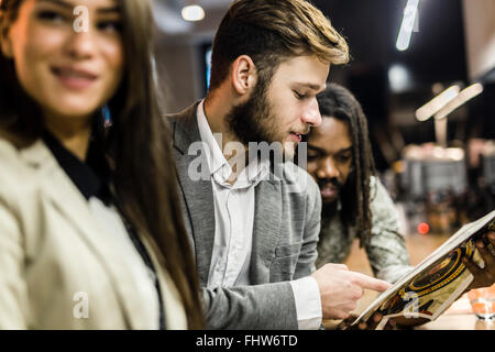 People discussing article in a pub after work - Stock Photo