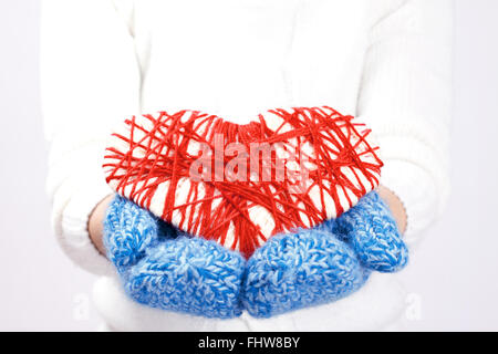 Warm dressed woman holding knitted red heart in her hands in blue mittens. Symbol of St. Valentine's Day - Stock Photo