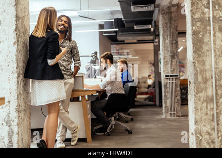 Business colleagues talking in the office  and smiling - Stock Photo