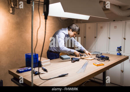 Joiner working and designing on workbench in workshop - Stock Photo