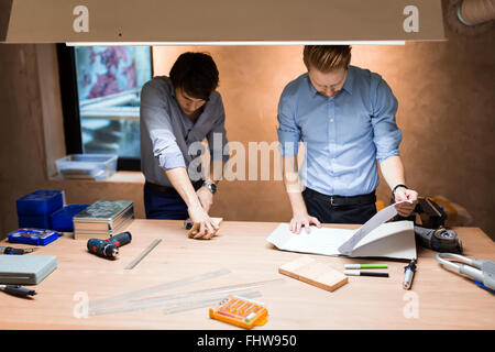 Two creative designers working in workshop and creating custom furniture - Stock Photo