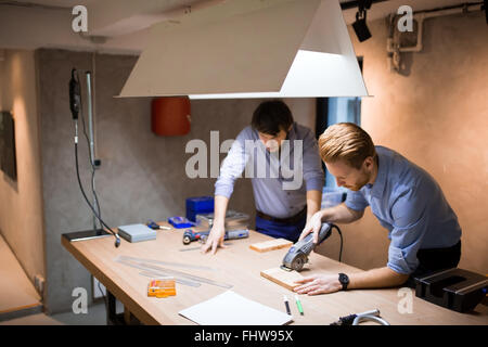 Two creative designers working in workshop with precision tools manufacturing a new product - Stock Photo