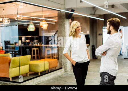 Beautiful saleswoman talking to customer and smiling - Stock Photo