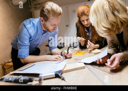 Classmates working on a project together and cooperating - Stock Photo