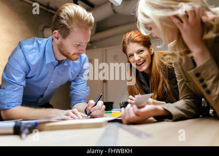 Team working on project together and sharing ideas in workshop - Stock Photo