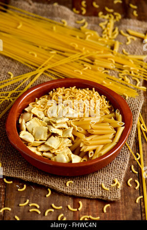 closeup of an earthenware bowl with different uncooked pasta such as ravioli, spaghetti or mostaccioli, on a rustic - Stock Photo