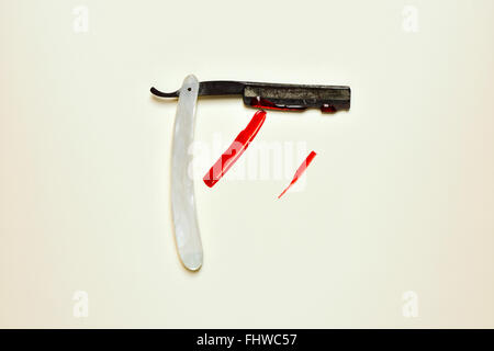 an old and rusty straight razor full of blood on an off-white background - Stock Photo
