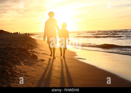 Walking on the beach, sunset. Children boy and girl playing on the sea shore on a sandy beach during sunset - Stock Photo