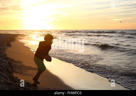 Sunset over the sea. Fun at sunset. Happy day. Walking on the beach, sunset - Stock Photo