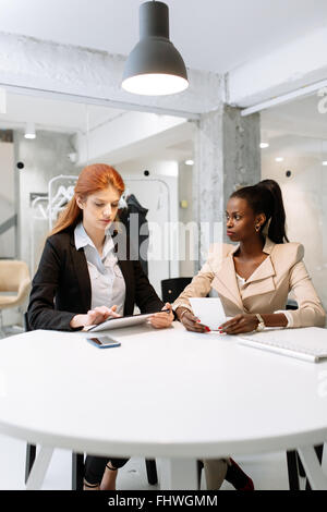 Two attractive businesswomen using technology while sitting in immaculate office - Stock Photo
