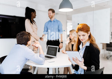 CEO of company holding tablet at board meeting while staff is discussing new strategy - Stock Photo