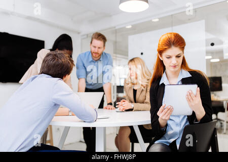 Business colleagues sitting at desk with technology at hand - Stock Photo