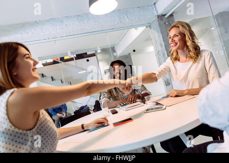 Female coworkers shaking hands and greeting each other while sitting at a table - Stock Photo