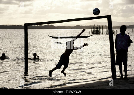 Boys playing ball on the seafront in Praia de Dentro - Peninsula de Marau - Stock Photo