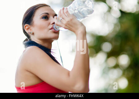 Attractive woman drinking water after running - Stock Photo