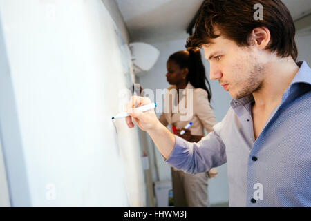 Smart people writing on whiteboard in search of a solution - Stock Photo