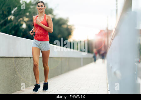 Woman jogging in city and listening to music - Stock Photo