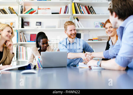 Successful partnership in business displayed by shaking hands in office - Stock Photo