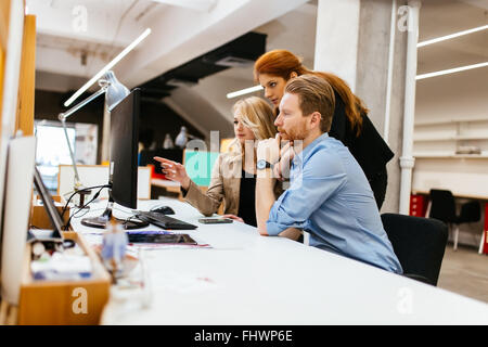 Designers working as a team in office discussing future trends - Stock Photo