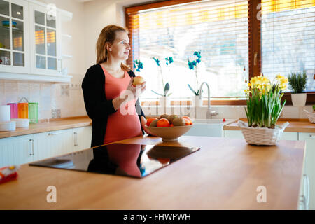 Pregnant woman eating fruit in modern kitchen - Stock Photo