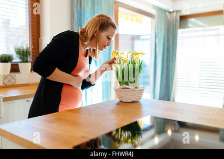 Pregnant woman taking care of flowers in modern kitchen - Stock Photo