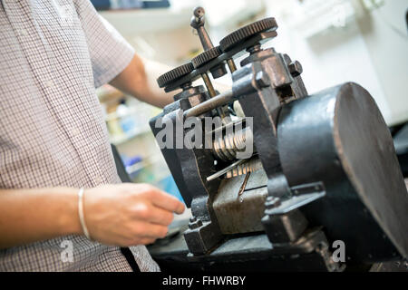 Goldsmith crafting metal with the help of a press - Stock Photo